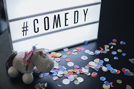 Comedy-Schriftzug mit einem Pummeleinhorn im Vordergrund