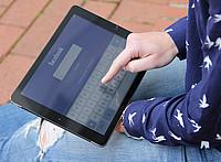 Hand die auf einem Tablet in der Facebook App tippt