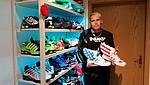 Mann hält zwei ausgefallene Sneaker mit Sternen und Streifen hoch