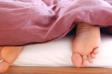 Füße schauen unter einer roten Bettdecke hervor