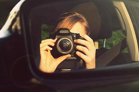 Frau fotografiert in den Rückspiegel