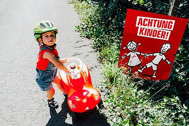 """Kleinkind mit Bobbycar am Straßenrand vor """"Achtung Kinder""""-Plakat"""