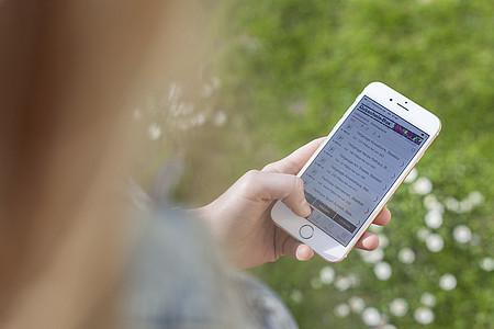Frau hält iPhone in der Hand während sie auf der Wiese steht