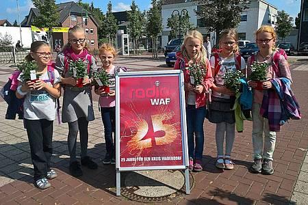 Gruppenfoto mit Schülerinnen, die eine Blume von Radio WAF geschenkt bekommen haben